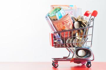 Tenge. Kazakh money in shopping cart on white background close-up..