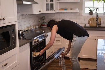 Woman putting patties inside oven in kitchen
