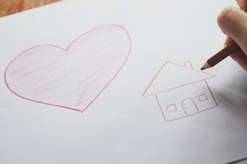 Hand with color pencil drawing heart and house,happy home concept.