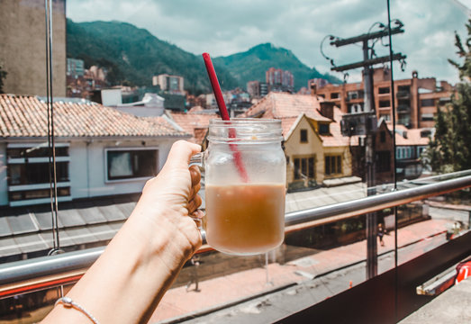 Caucasian millennial woman holds up iced coffee against a view of Bogota, Colombia