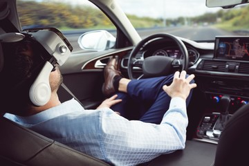 Businessman using virtual reality headset in a car