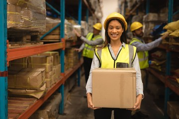 Female Staff holding cardboard box in warehouse