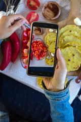 Woman hands make photography of food with phone. Red bell pepper salad with naan garlic flat bread  Smartphone photo of lunch for social media or blogging. Raw vegan vegetarian healthy food