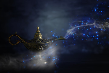 Image of magical mysterious aladdin lamp with glitter sparkle smoke over black background. Lamp of wishes.