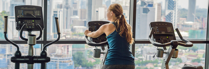 Young woman on a stationary bike in a gym on a big city background BANNER, long format