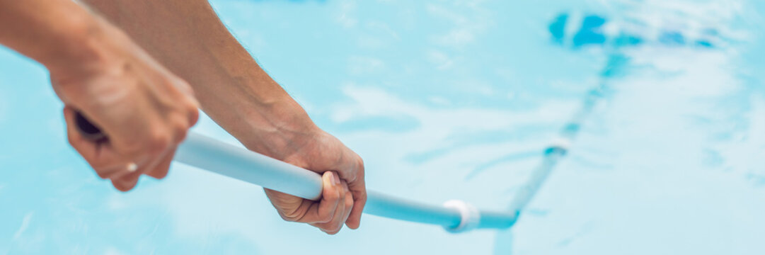 Cleaner of the swimming pool . Man in a blue shirt with cleaning equipment for swimming pools, sunny BANNER, long format