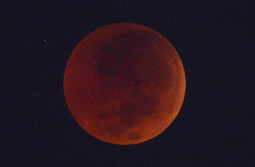 The full moon is seen during a lunar eclipse in the sky over Jakarta