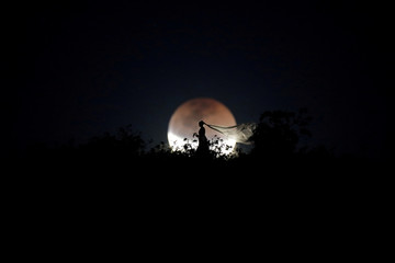 A bride poses for photo during a total lunar eclipse in Brasilia