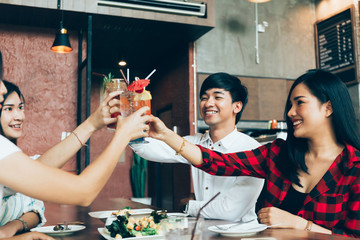 Group of Asian happy and smiling young man and women holding an alcoholic cocktail for toasting and celebrating in social party in restaurant.