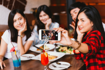 Group of Happy Asian male and female friends taking a selfie photo and having a social toast together in restaurant.