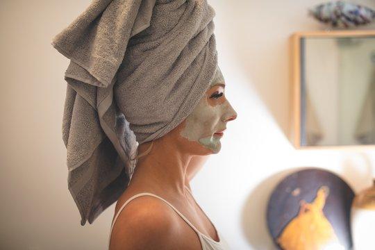 Pregnant woman with facial cream in bathroom