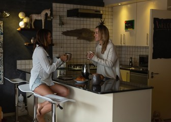 Lesbian couple having coffee in kitchen
