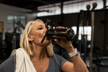 Mature woman drinking water in the gym
