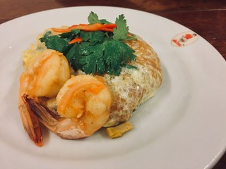 Top view of a Shrimp Pad Thai, traditional Thai dish with stir fried rice noodles with big shrimps, you can try to eat Pad Thai on the street in Bangkok, Thailand, Street food of Bangkok, Thailand