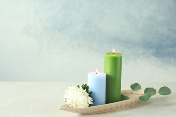 Candles with floral decor on table against color background