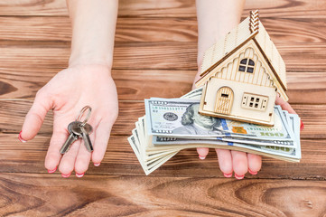 Woman's hands holding money, model of house and keys of house in palms over wooden table.