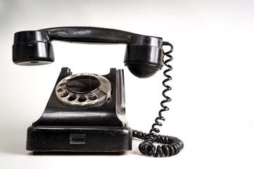 Old black telephone on white