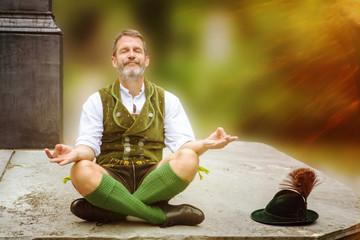 bavarian man sitting on wall and meditating