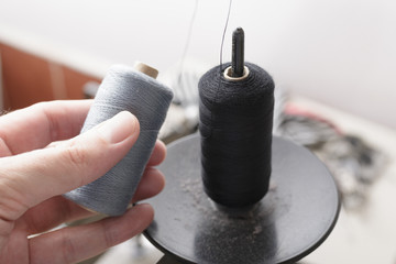 Spool of Black Thread on Pin and Gray Thread in Hand Fototapete
