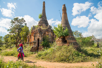 Local people walking pass Nyaung Ohak pagodas the group of ancient pagodas in Indein village West of Inle Lake, Myanmar.