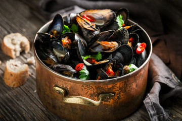 Mussels with coriander and chili peppers on wooden table