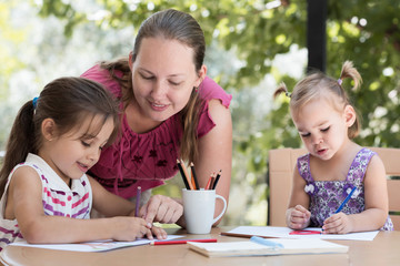 Happy Smiling Mother And Child Daughters Having Fun and Drawing Pictures Outdoors in Garden in Summer Season