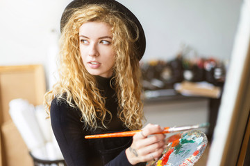 Tattoed blonde curly artist in black hat holding brush and palette with oil behind the easel in light studio, she looking to the window