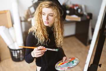 Blonde curly feemale artist in black hat holding brush and palette with oil behind the easel in light studio, she looking to the window