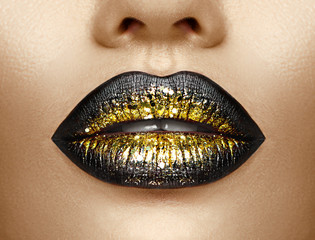 Lips makeup. Beauty high fashion gradient lips makeup sample, black with golden color. Sexy mouth closeup. Lipstick