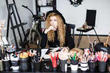 Blonde long hair curly feemale artist in black hat sitting behind the table with art stuff in her studo