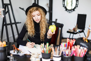 Romantic blonde long hair curly feemale artist in black hat sitting behind the table with color pencil and holding green apple