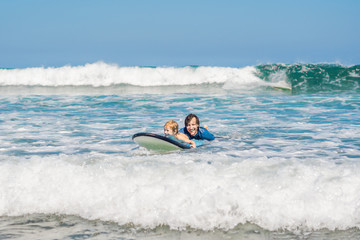 Father teaching his young son how to surf in the sea on vacation or holiday. Travel and sports with children concept