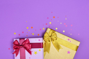Colored shiny classic gift boxes with satin bows and confetti in the shape of stars as attributes of party