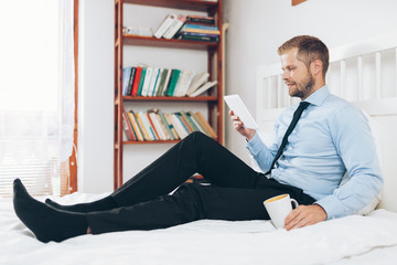 Businessman on bed working with a tablet from his hotel room