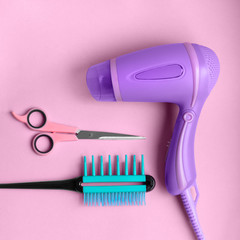 Hairdressing tools poster Scissors, hair dryer and flat comb are lying on pink background Flat lay photo