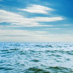 blue sea closeup and white clouds in sky
