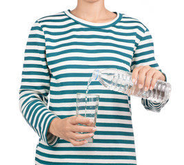 girl dressed in long sleeve shirt pouring water from bottle in to glass. isolated on white background