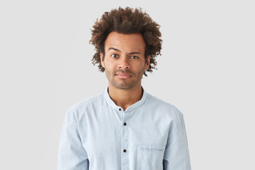 Puzzled mixed race young male with Afro hairstyle raises eyebrow in bewilderment, reacts on something, feels doubt, dressed in elegant shirt, isolated over white background. Ethnicity concept