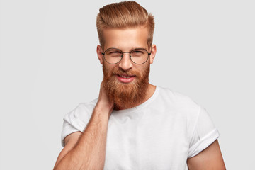 Cheerful ginger male with thick beard and mustache, looks mysteriously through spectacles, wears casual shirt, ready for work stands alone against white background. People, emotions, lifestyle concept