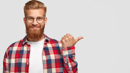Cheerful bearded male has charming smile, points aside, shows nice place to visit, attracts your attention, dressed in stylish clothes, has trendy hairstyle. People, style, advertisement concept