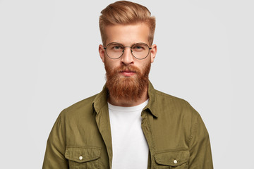 Serious unshaven man with ginger hair and beard, looks directly at camera, thinks about something, wears fashionable shirt and round spectacles, isolated over white background. Masculinity concept