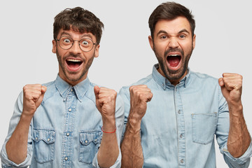 Wall Mural - Glad male football fans shout for their favourite team, clench fists, feel joyful of victory, dressed in denim shirts, isolated over white background. Two cheerful companions celebrate something