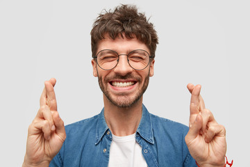 Happy unshaven male with broad smile, shows white teeth, crosses fingers for good luck, being in high spirit stands over white background wears fashionable denim shirt. Positive guy makes hope gesture