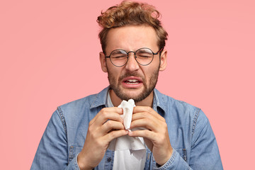 Portrait of allergic male sneezes all time, rubs nose with handkerchief, has sick look, suffers from cold, has displeased facial exression, wears denim shirt, isolated on pink. People, disease concept