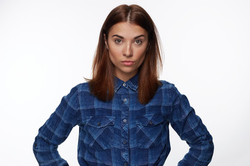 Horizontal indoor studio shot of skeptical young mixed race woman feeling suspicious, her look expressing disapproval or doubt, keeping arms on hips, having a suspicion that  husband cheated on her.