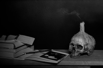 Skull with candle on head which has do not lighting for read and learn on the wooden plank in dark room