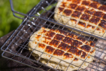 Top view on two grilled slices of homemade halloumi cheese on grill. Outdoors..Grilling season.
