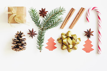 Christmas and New Year composition. Gift box with ribbon, fir branches, cones, star anise, cinnamon, candy cane and paper christmas tree on white background