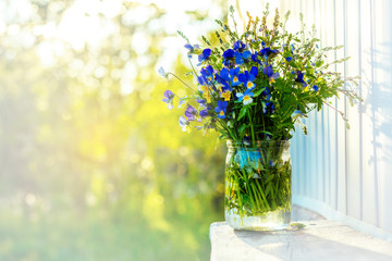 Bouquet of wild pansies in vase on nature background