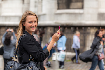 Smiling Young Woman with Mobile Phone with Out-of-Focus People Behind Her
